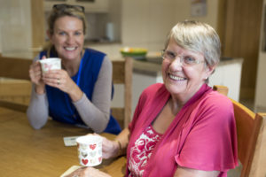 Community care worker joins an an elderly woman for a cup of tea while sitting at her kitchen table